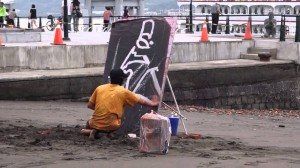 海で絵を描いているアーティスト、最初はなんだか分からないがひっくりかえすと・・・